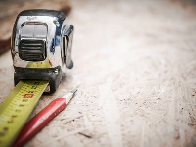 Close-Up Of Tape Measure And Pencil On Wood