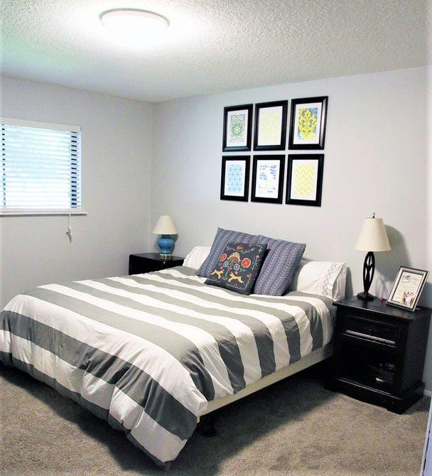 Dormitorio gris con manta gris y dos mesitas de noche