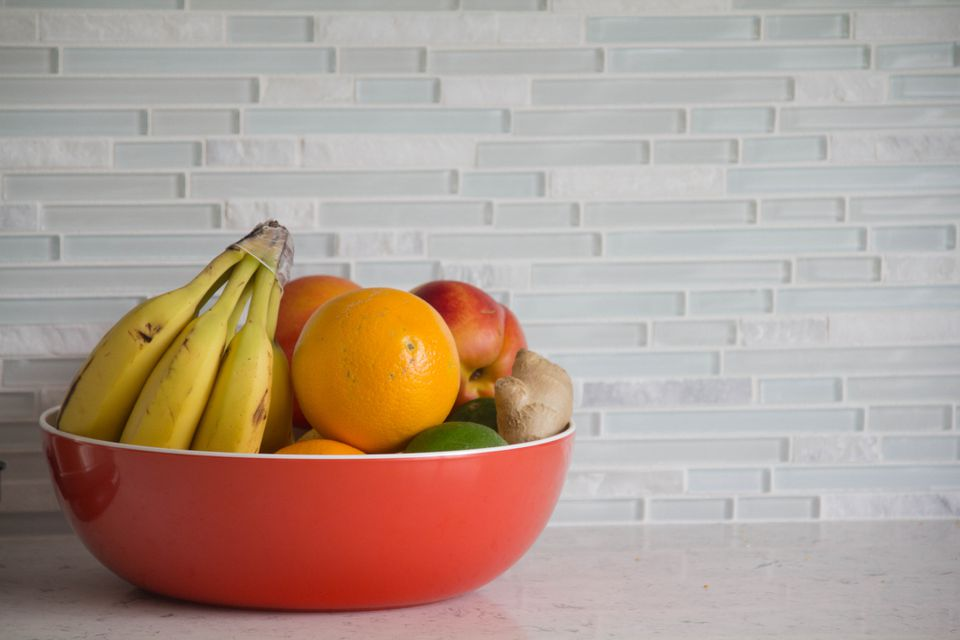 Fresh fruit in red bowl with a glass backsplash