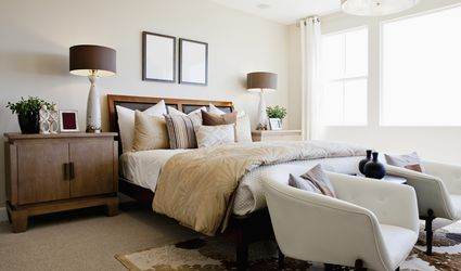 White bedroom with two arm chairs in front of made up bed.