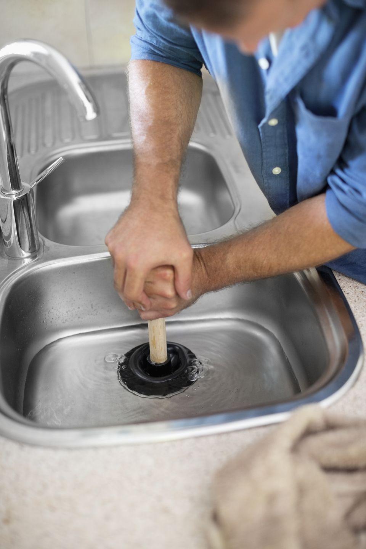 Plumber unclogging kitchen sink