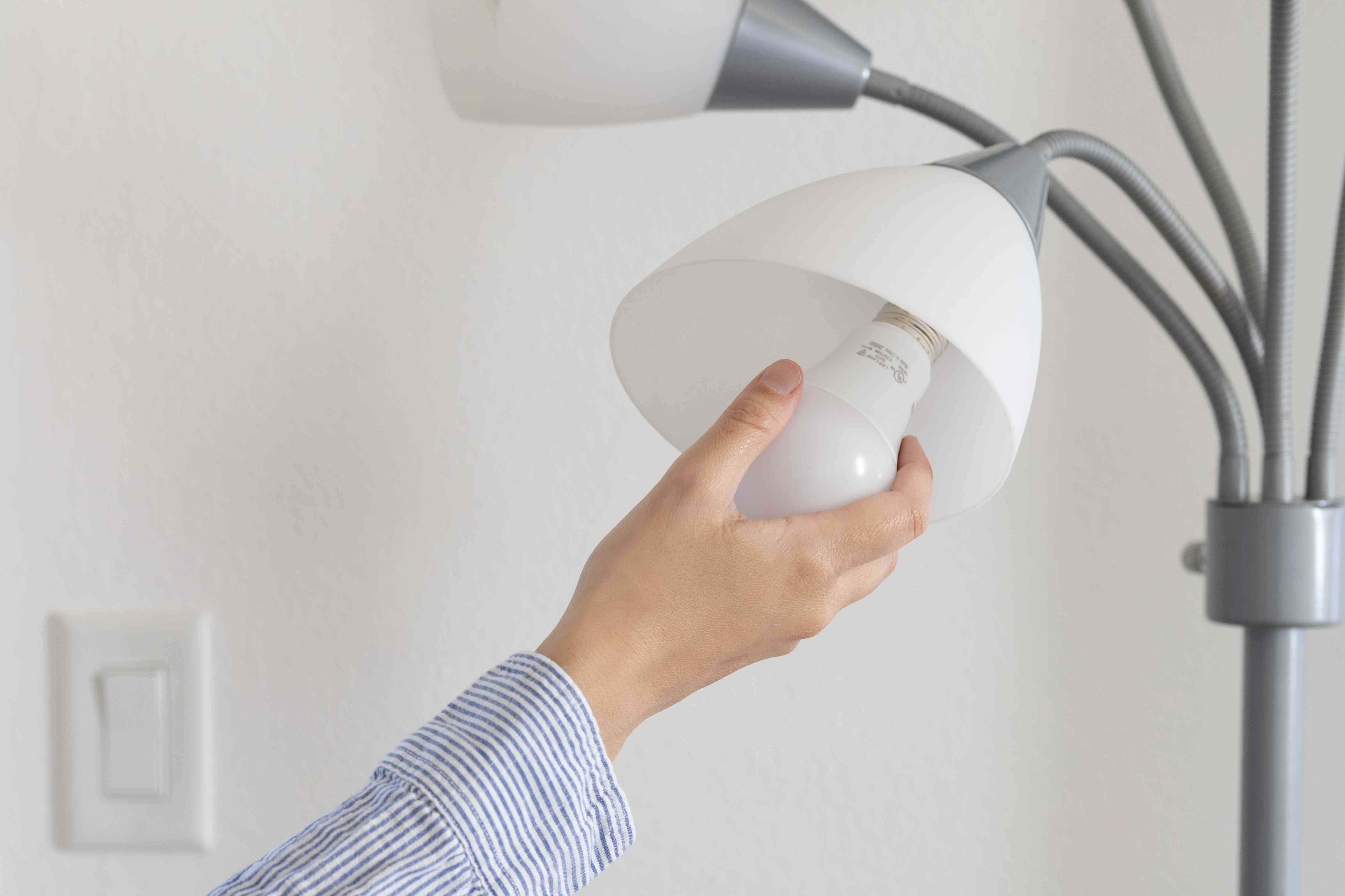 LED light bulb being inserted into gray lamp to lower electric bill