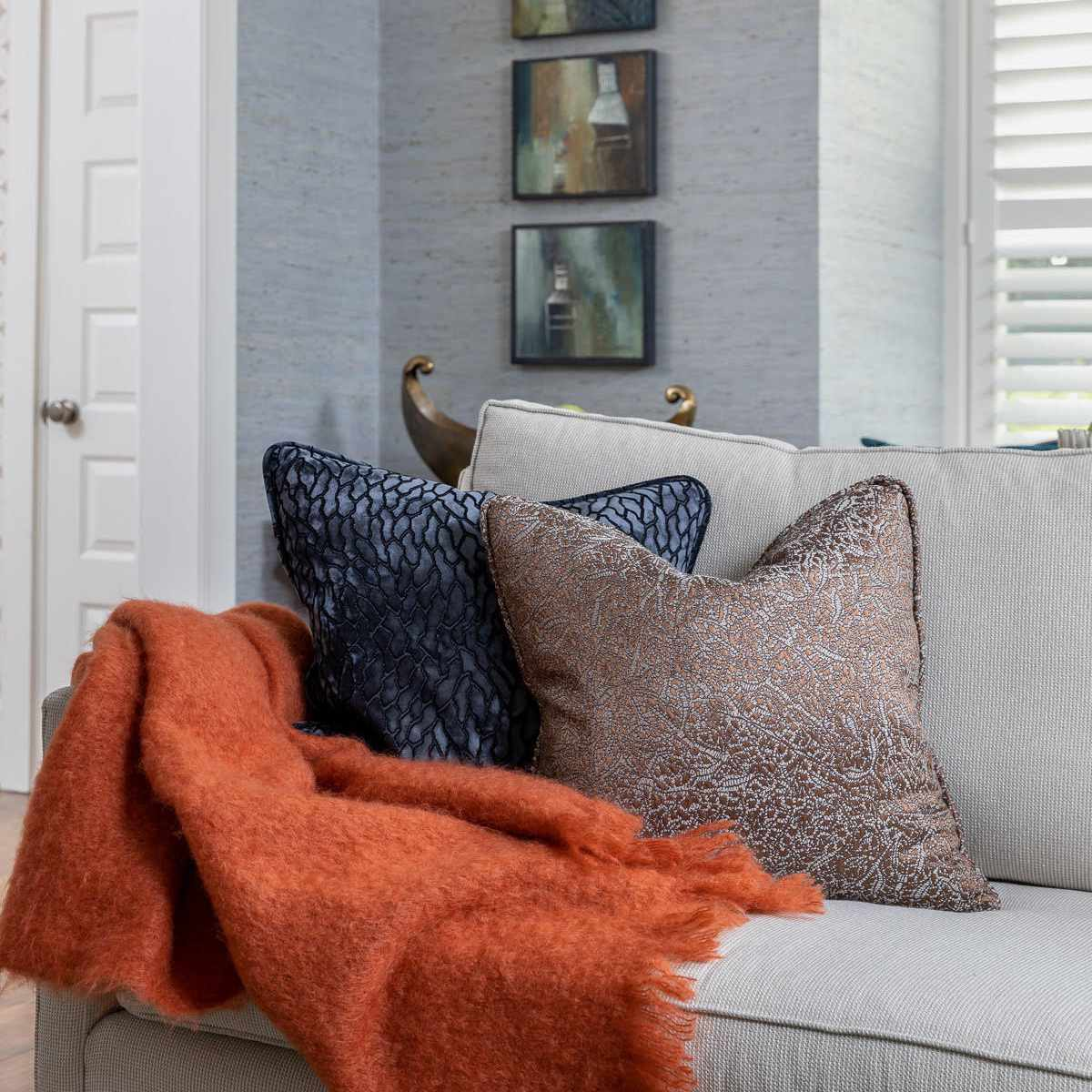 a living area with fall decor features a cozy orange throw blanket