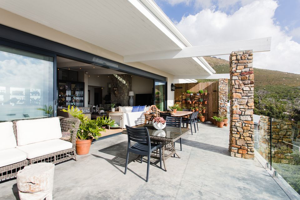 Open patio with outdoor furniture and brick pillar in sunlight