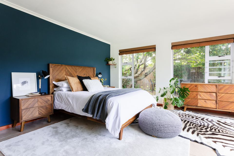 Bedroom with navy blue wall, mid-century modern and wood furniture and large windows