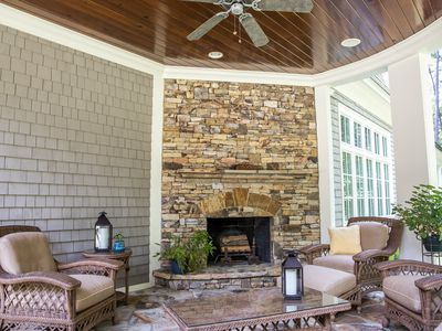 Back Stone Patio Porch of large Home with an outdoor fireplace