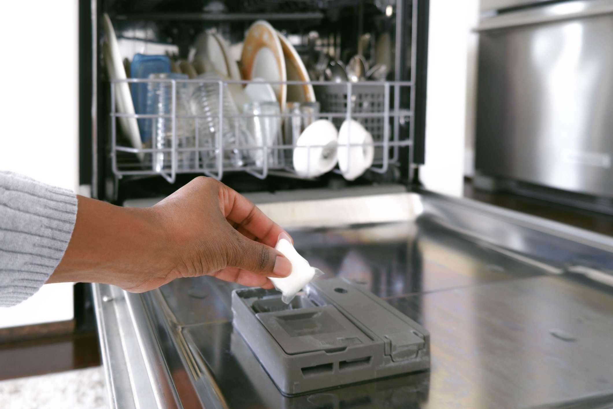 A woman putting a dishwasher pod into a dishwasher