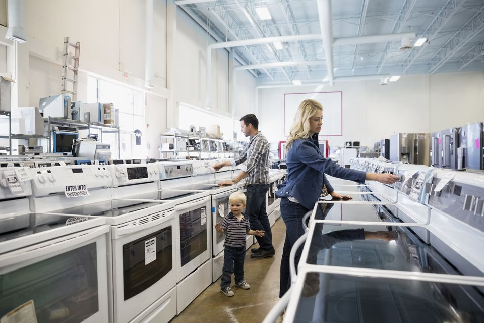 Young family shopping for stoves in appliance store