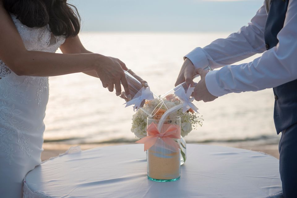 Midsection Of Wedding Couple Putting Sand In Container On Table At Beach