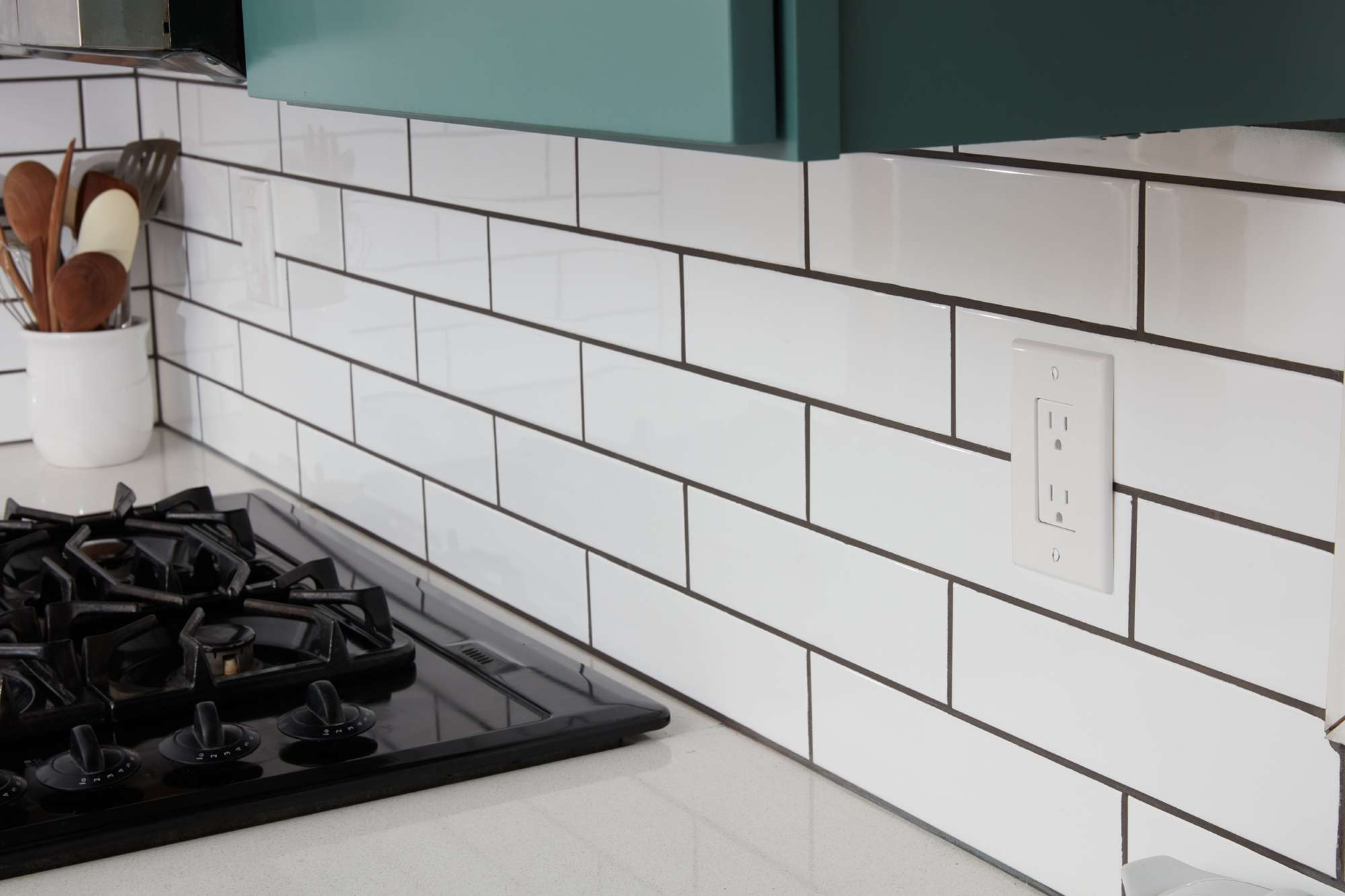 Kitchen electrical outlet on tiled wall next to stove