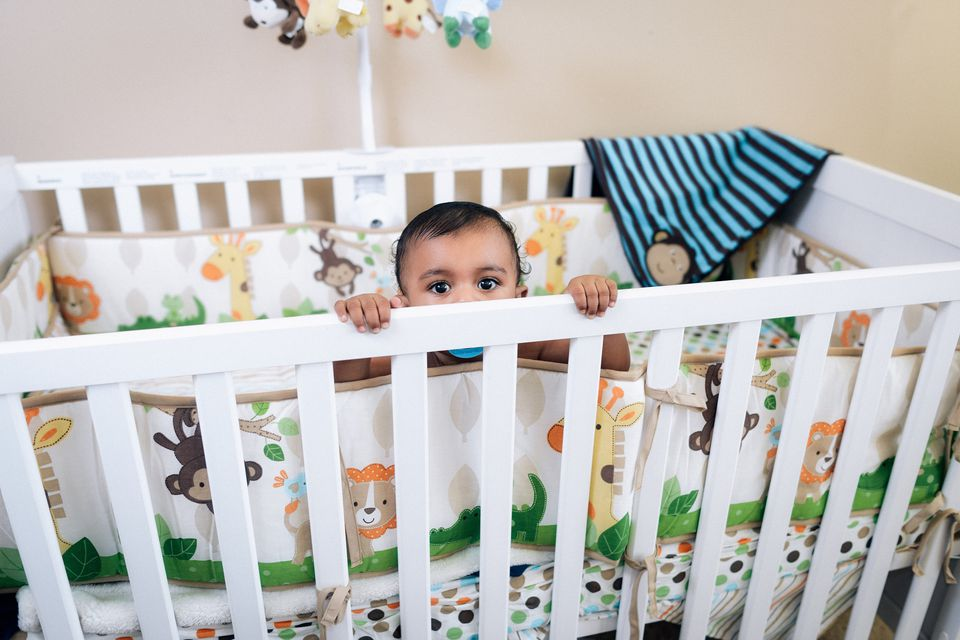baby boy peeking over the top of crib bumper