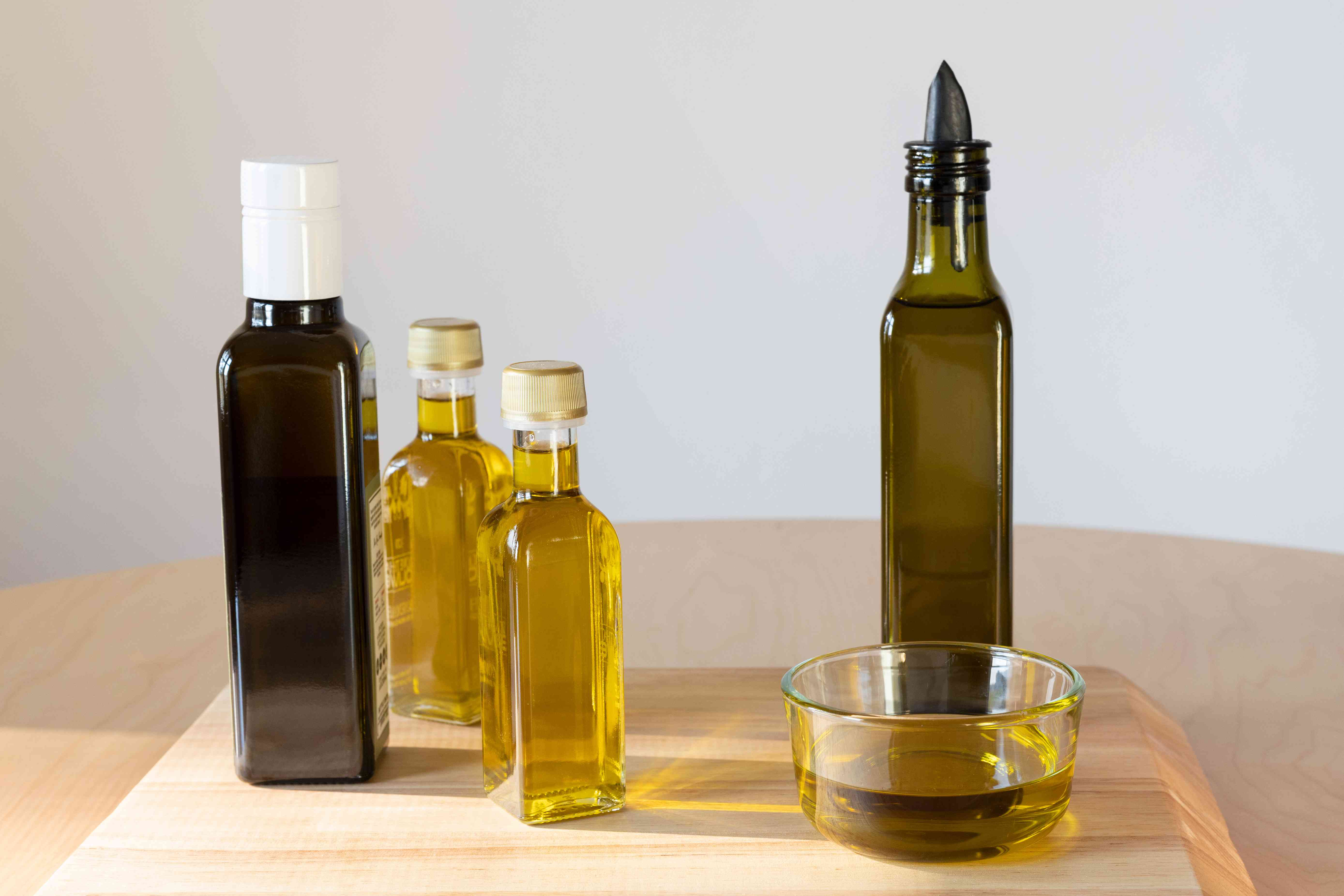 Vegetable oil in tall glass containers on wooden surface