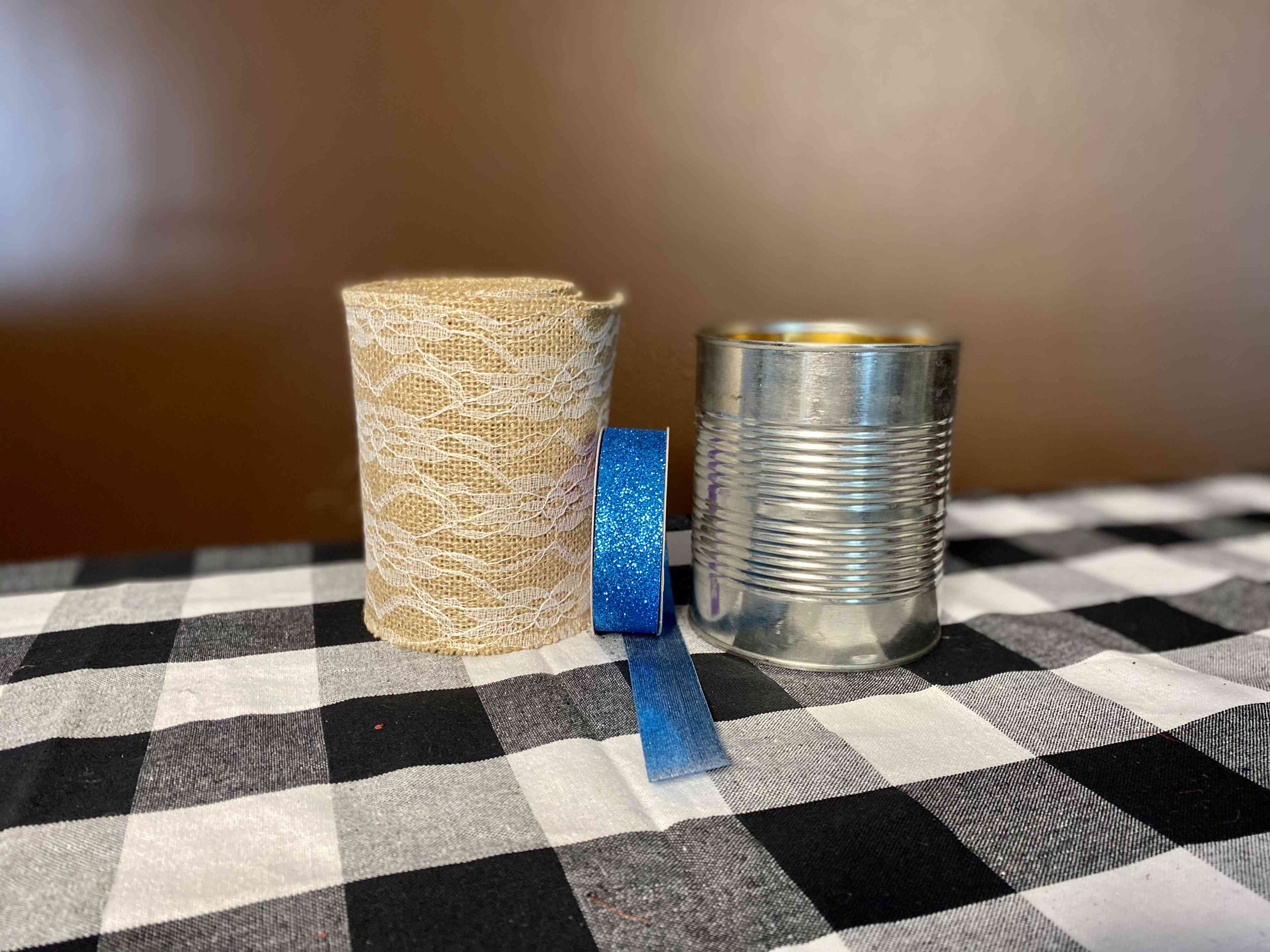 Homemade centerpiece made from a can, burlap, lace, and ribbon