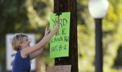 Caucasian woman hanging yard sale sign