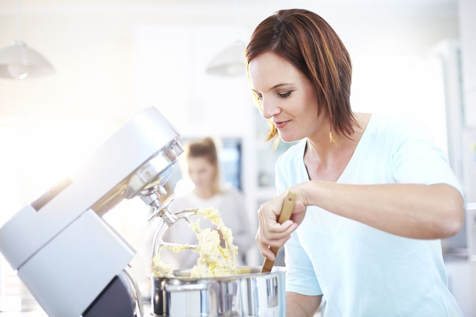 Woman baking with stand mixer in kitchen