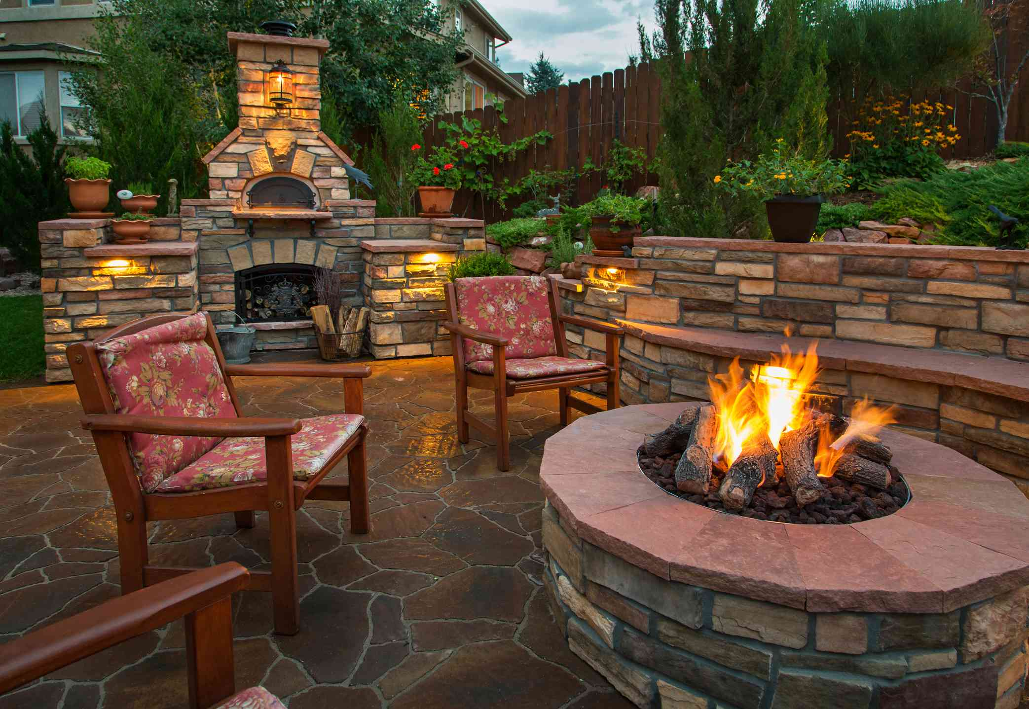 Stone built fire pit and pizza oven with matching retaining wall