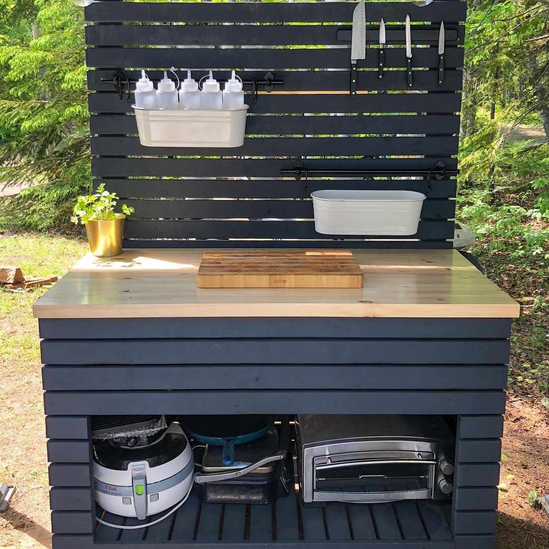 A DIY outdoor kitchen table with shelving and storage buckets.