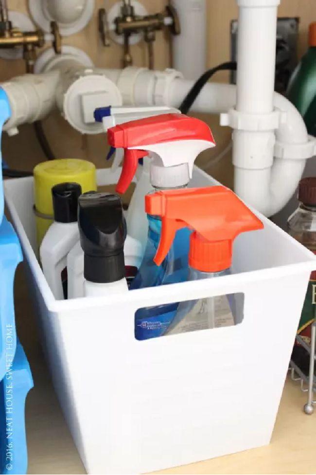 A white bin full of spray bottles.