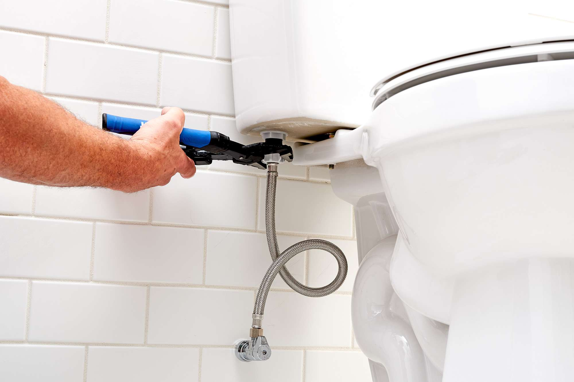 Supply line disconnected from toilet's fill valve with channel-lock pliers