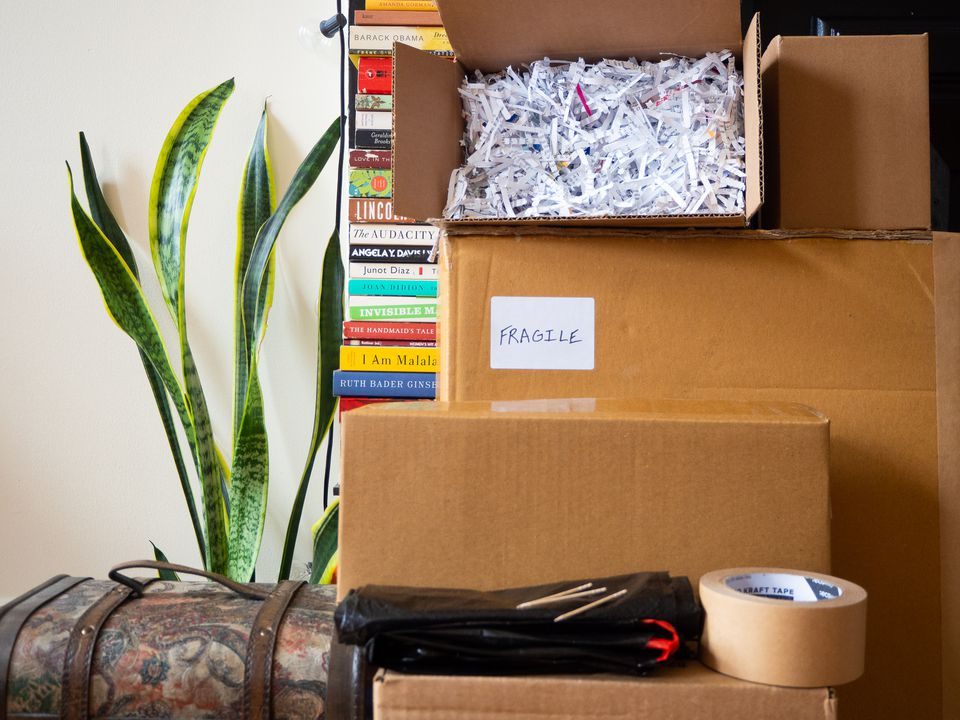 Stacked moving boxes with shredded paper for packing, roll of tape, garbage bag and toothpicks next to houseplant and books