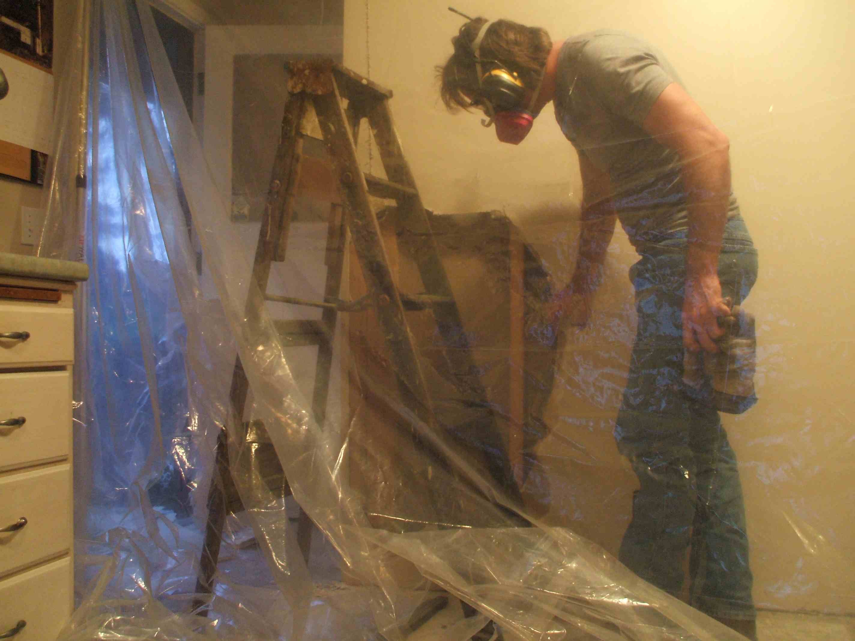 A man pulling out sections of drywall