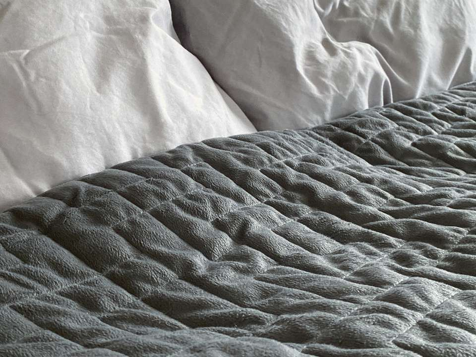 Gray weighted blanket on bed
