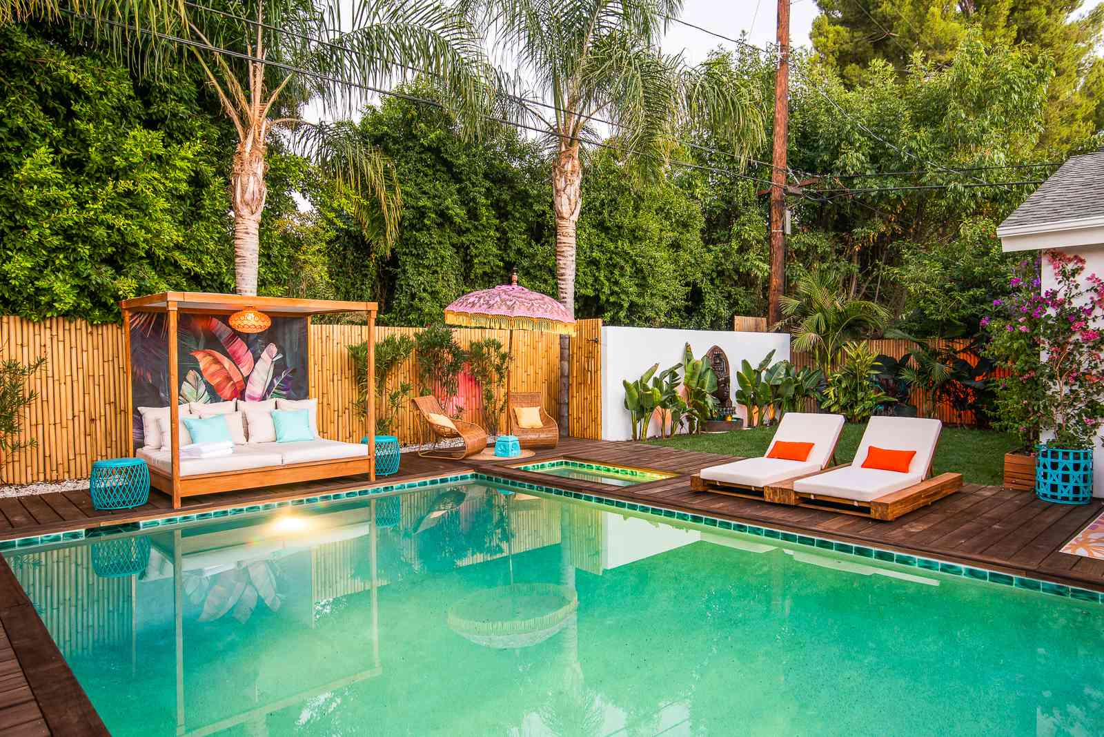 Outdoor pool area with bamboo fencing and day bed