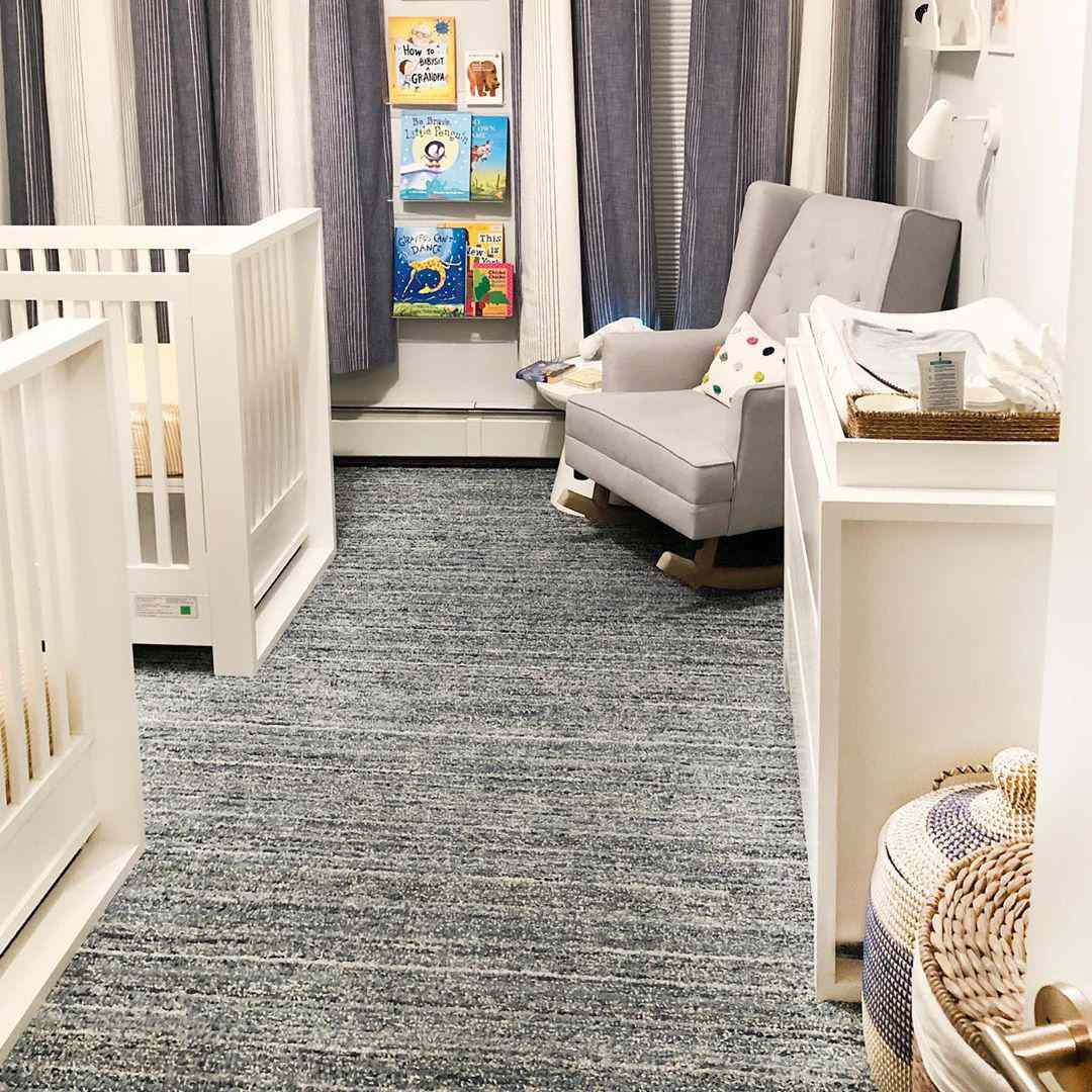 Nursery with two cribs and a gray carpet
