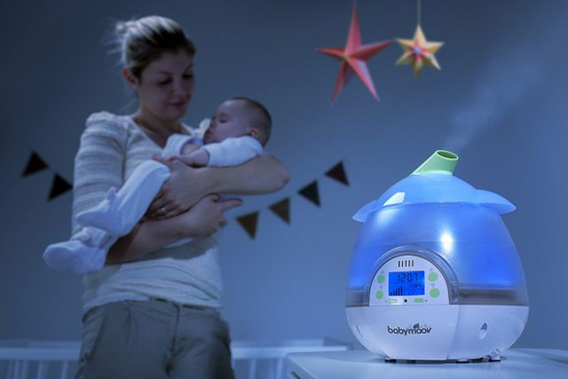A mother holding her child by a Babymoov humidifier