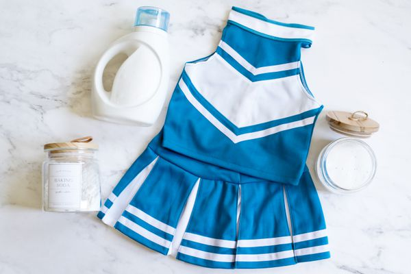 Blue and white cheerleading uniform next to laundry detergent bottle and baking soda glass containers