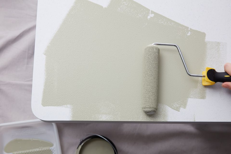 Cream paint on paint roller going over laminate surface