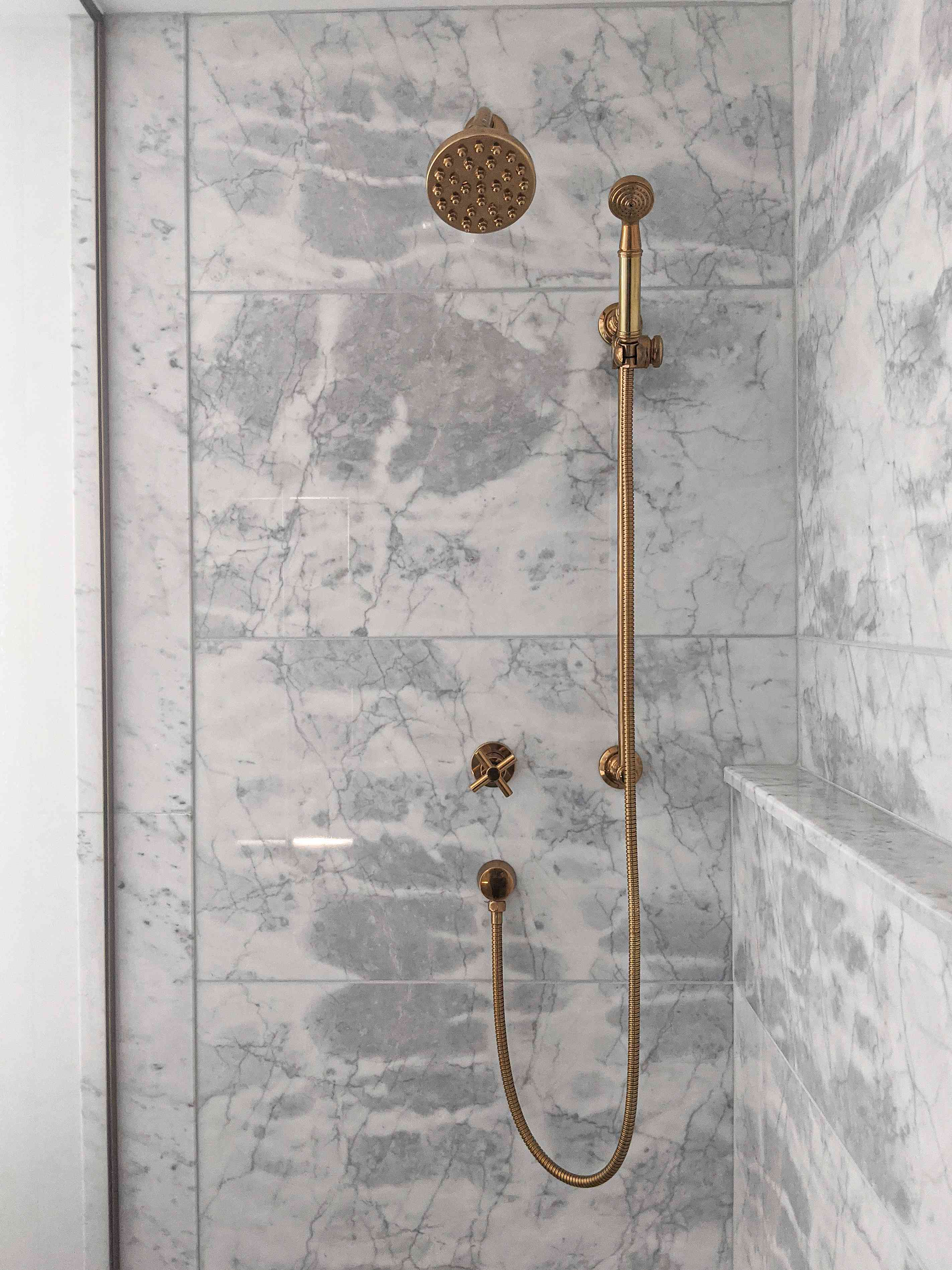 The shower in the primary bathroom of Molly & Fritz features marble walls and brass-tone hardware