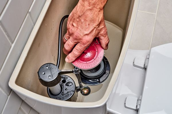 Leaky toilet flush valve being replaced inside toilet tank
