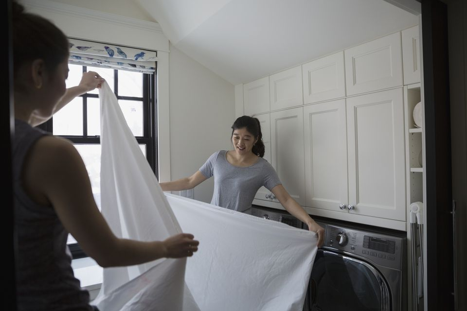 Mother and daughter folding bed sheet