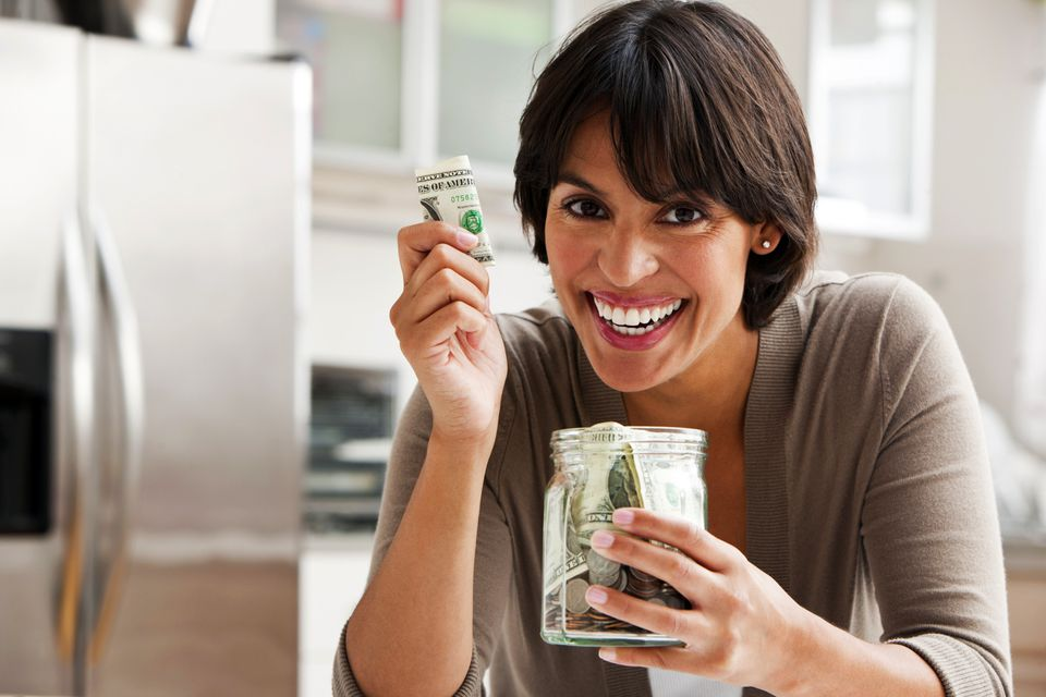 Woman holding dollar bill and a jar full of money