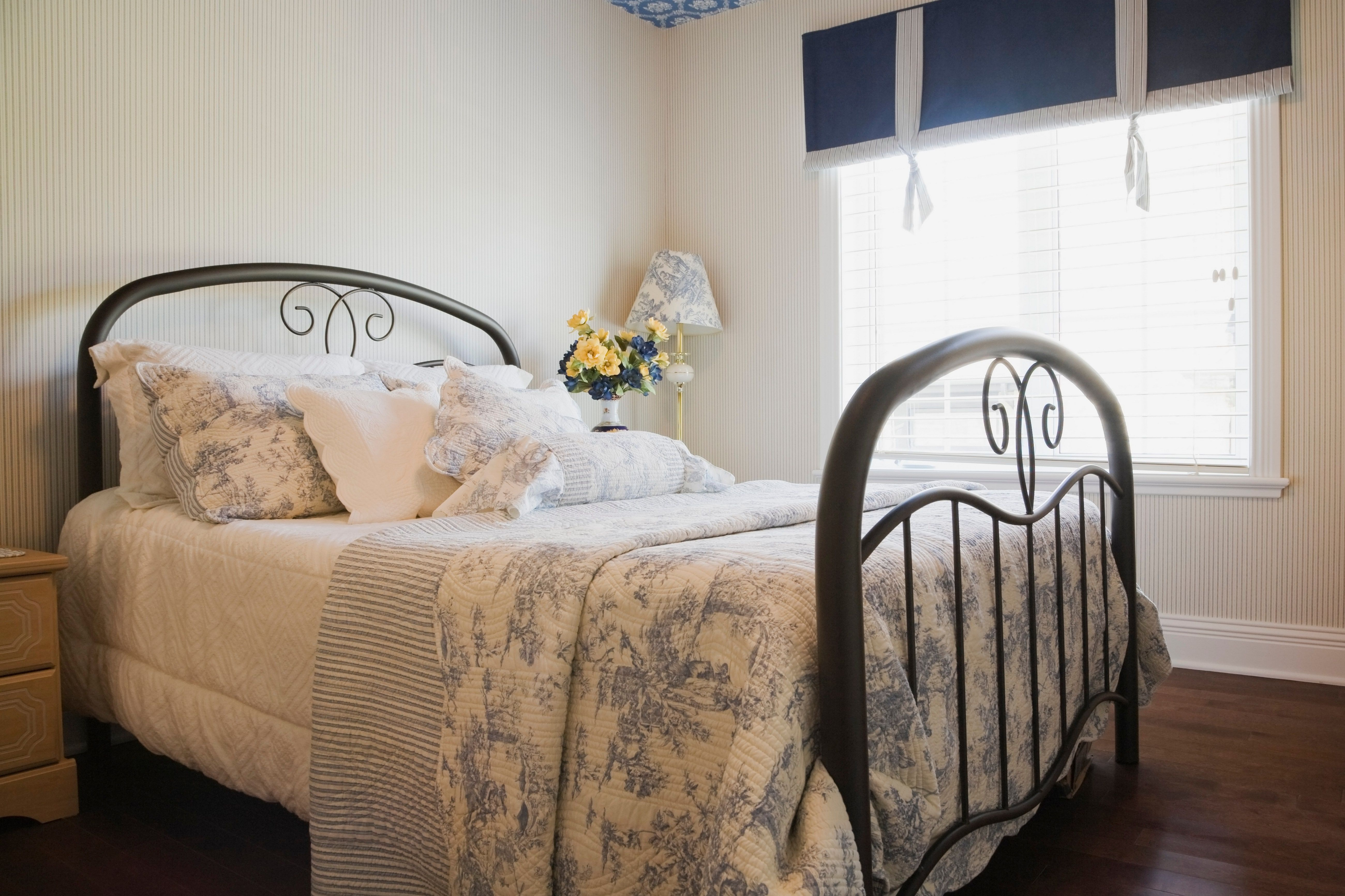 Shabby Chic bedroom with quilt and iron bed.