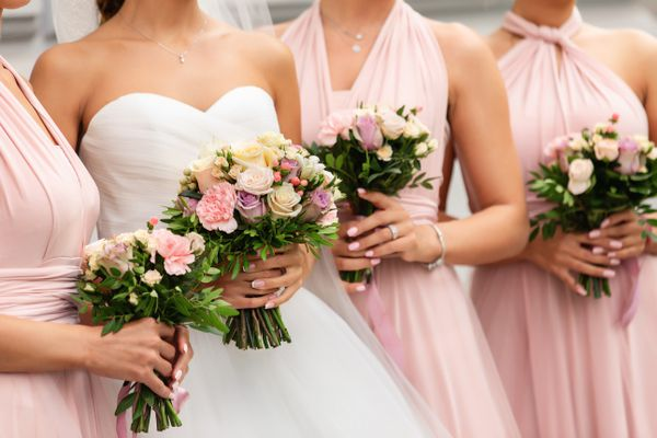 Bride and bridesmaids in pink dresses posing with bouquets at wedding day. Happy marriage and wedding party concept