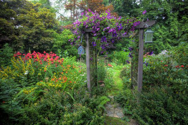 An arbor at the entrance of a garden path.