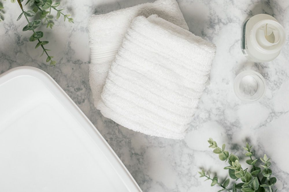 White containers and towels for washing crochet blankets