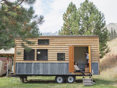 two people in the doorway of a tiny house made of wood