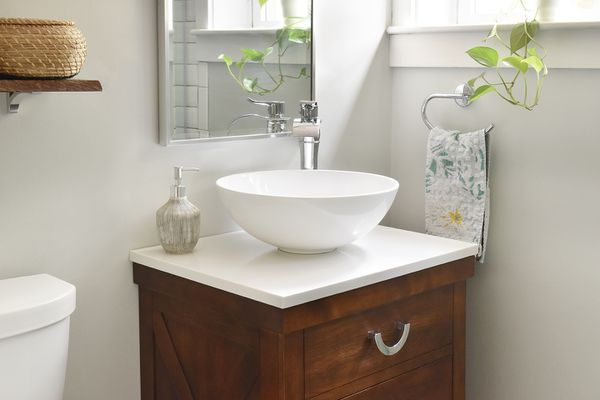 White vessel sink with wooden cabinet next to hanging towel and houseplant