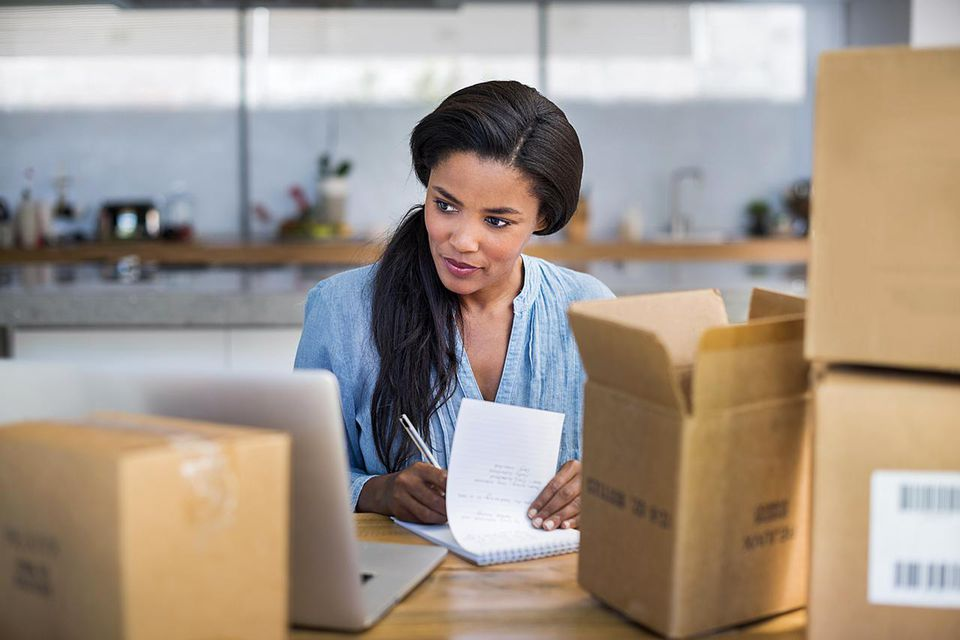 Woman making a list of things to do with packed boxes