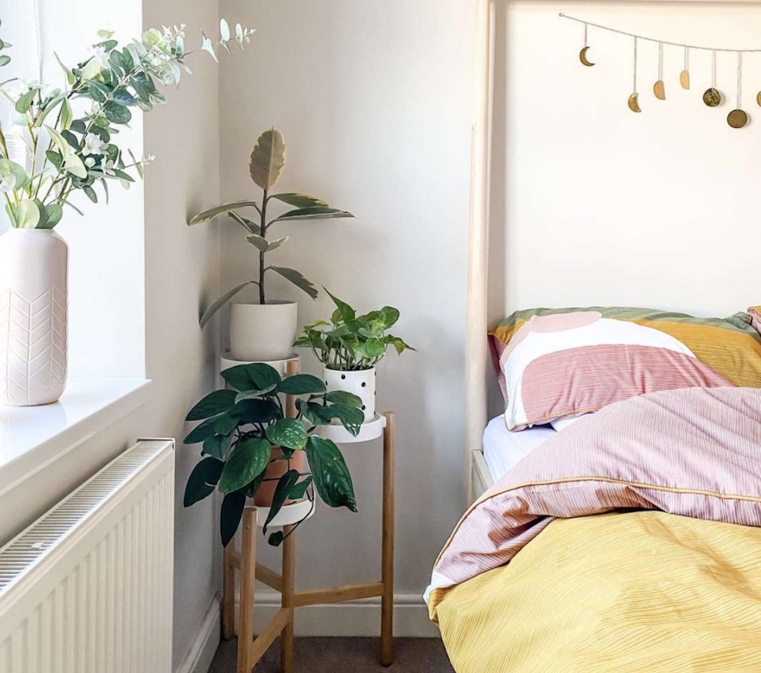 modern bedroom with plants on bedside table, yellow and pink comforter