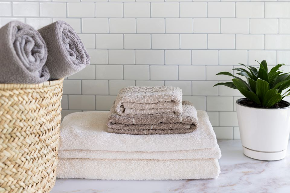 White and tan towels folded in bathroom next to houseplant and wicker basket with rolled gray towels