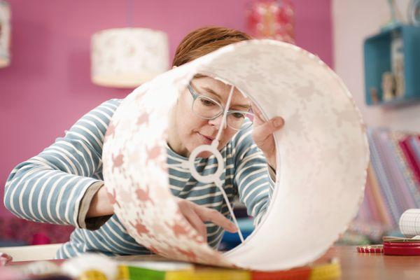 A woman making a custom lampshade