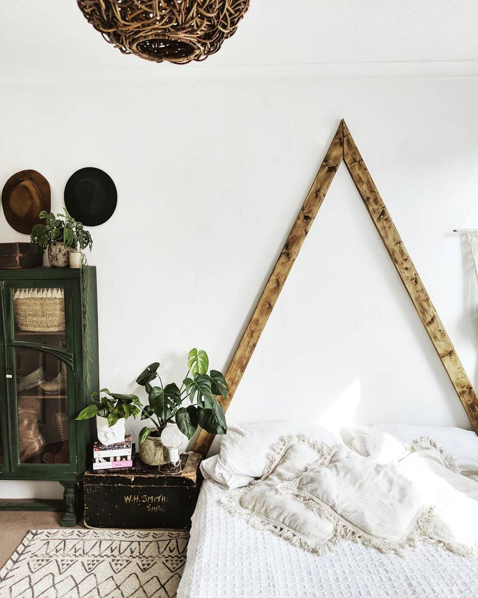 A boho bedroom with a wooden triangle behind the bed