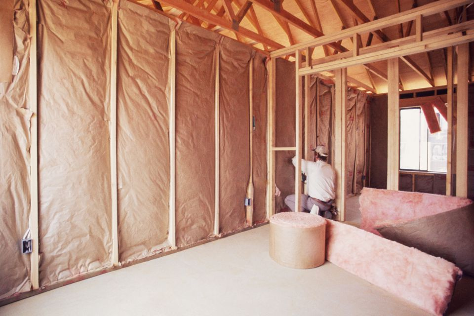 Man installing insulation in wall of new home