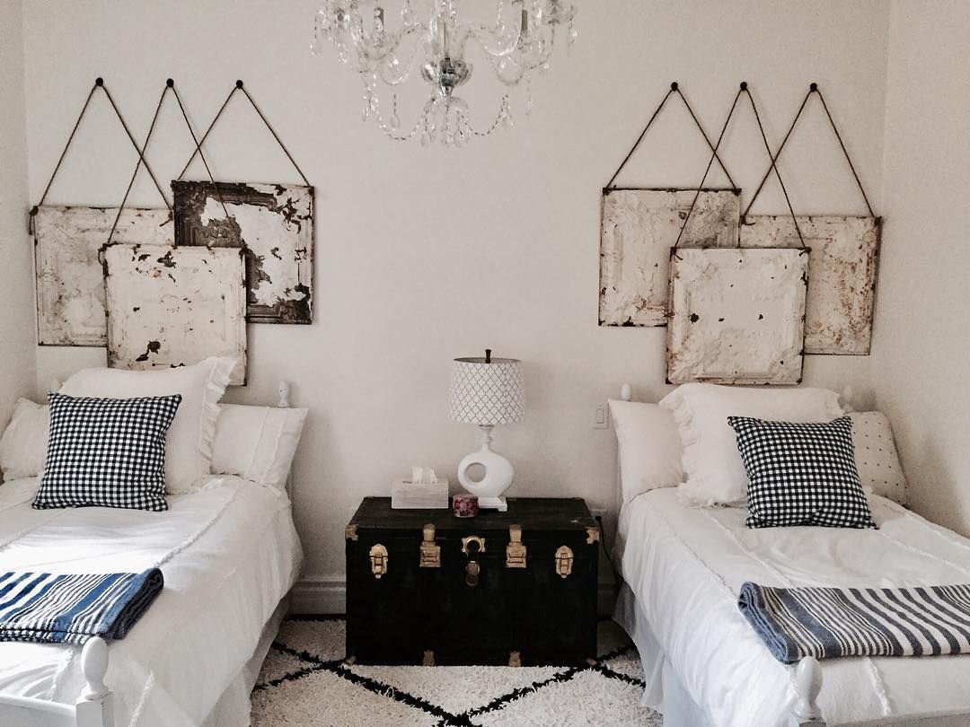 Two beds with tin hanging on the wall and a chest between the beds.