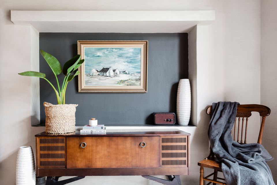 Charcoal gray wall in center of decorated living space with potted plant on wood table and wooden seat in right corner