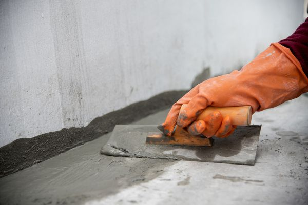 close up hand labor hold trowel masonry work in construction site